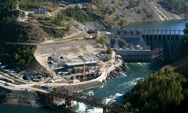 An area view shows the Waneta Expansion's powerhouse being built into a hill against the Pend d'Oreille River.