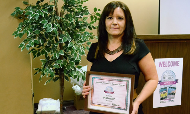 Wendy Franz of Imagine Ink and I Love Creston holds her Influential Women in Business Award certificate.