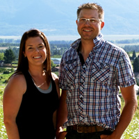Amy White and David Mutch stand at the top of a hill overlooking their orchard at JRD Farms.