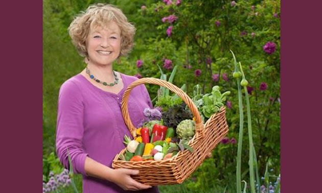 A women wears a pink cardigan and holds a basket overflowing with produce.