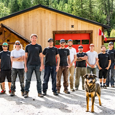 A large crew of men and one dog are lined up in a large vee in front of a shop. Rexxy, the dog, is the most distracting crew member. He shows true professionalism when welcoming people to the shop.