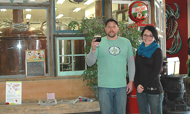 A man holding a glass of beer up and a women standing beside him.