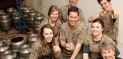 People sitting in a brewery with kegs