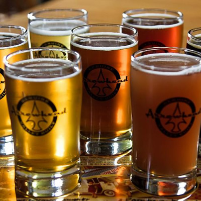 Picture of several glasses of Arrowhead Brewing Company beer, all of different shades.