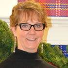 A sandy-haired woman with glasses wearing a black sweater.