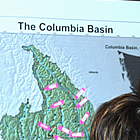 Three people stare at a map of the Columbia Basin.