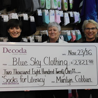 (L-R) Kim McBurney, Blue Sky human resource manager, Brenda Le Clair, CEO of Decoda Literacy Solution and Blue Sky owner/designer Marilyn Robison with Blue Sky's donation to the charity.