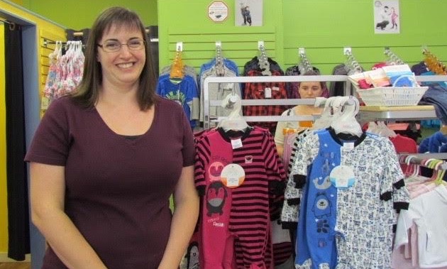 Megan Lescanec stands next to some baby clothes in her store, the Bumble Tree.