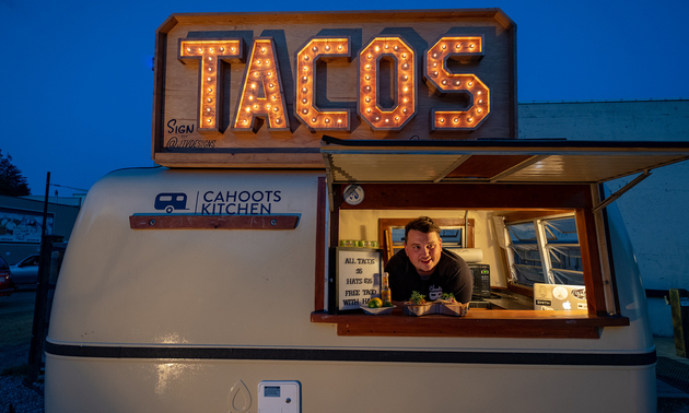 A taco truck with the owner, Spencer Moores, leaning out the window