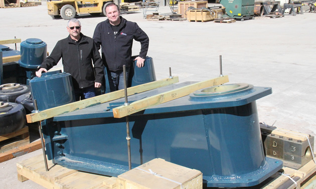 Two men standing in front of a large blue steel component for mining.
