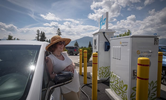 A woman with a hat leans on her car at a EV-charging station.