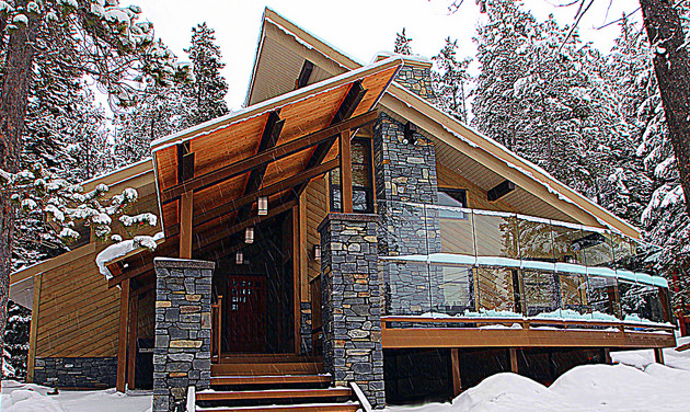 A Modern Mountain Alpine home design that includes a steep sloped roof, the combination of rock and wood work decoration and large glass windows.