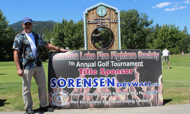 Rob Sorenson poses with last year's golf tournament banner.