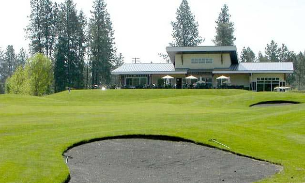 Sand trap in the foreground, with golf clubhouse in the background of picture.