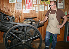 Man standing beside an old-fashioned letterpress machine in Fernie, BC