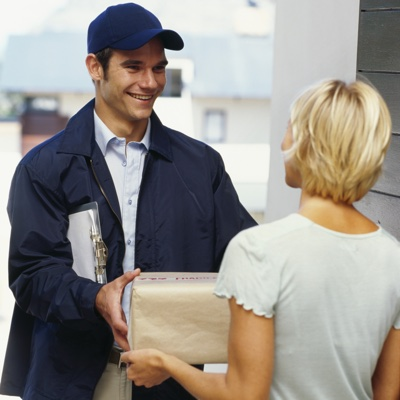 A delivery man wearing a navy blue baseball cap and jacket, handing a parcel to a young woman.