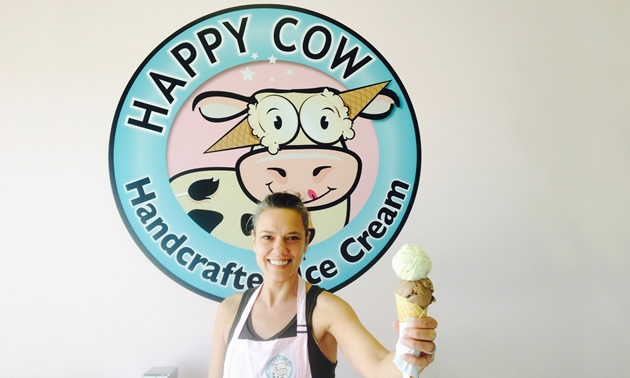 Co-owner Wendy Lyn holds out a two-scoop ice cream cone while standing in front of the Happy Cow Ice Cream's logo.