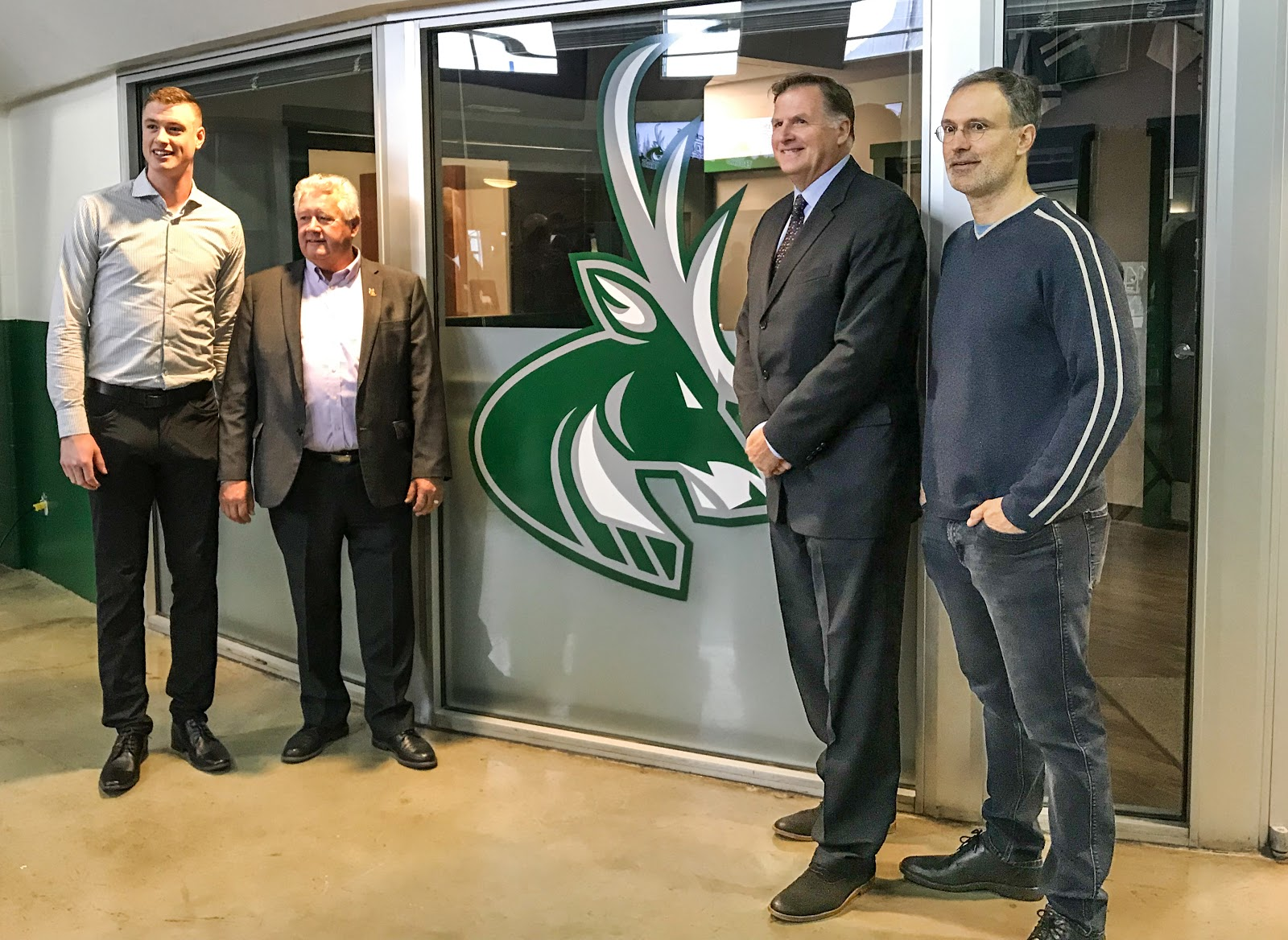 Nathan Lieuwen, majority owner; Lee Pratt, Cranbrook mayor; Chris Hebb, BCHL commissioner; and Scott Niedermayer, a Hall of Fame NHL defenceman and part owner of the new Junior Hockey franchise, stand in front of the new Cranbrook Bucks logo at Western Financial Place.