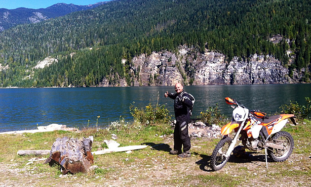 A man standing by a dirt bike and a lake.