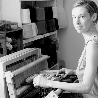 Dani Ortman, fibre artist, sitting at her loom.