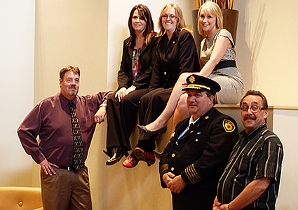 Photo of a group of people posing for a photo. Three women are sitting on a ledge and below are three men.