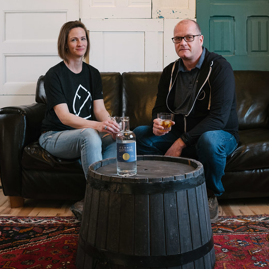 Owners of Fernie Distillers sitting beside a table with a bottle on it