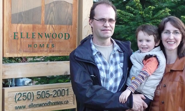 Man and woman standing together holding a young child in front of a wooden business sign