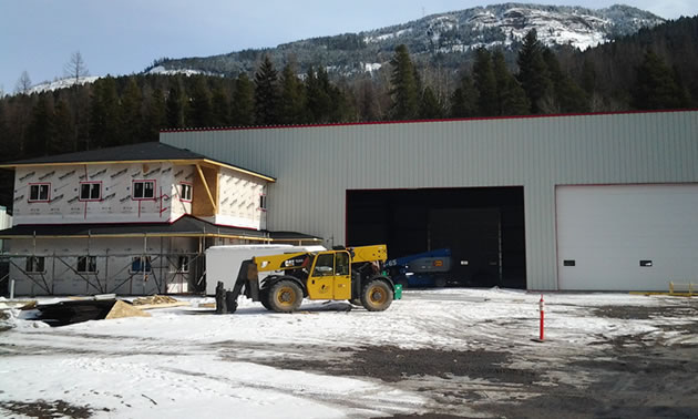 A yellow piece equipment in front of a large shop with the mountains in the background.