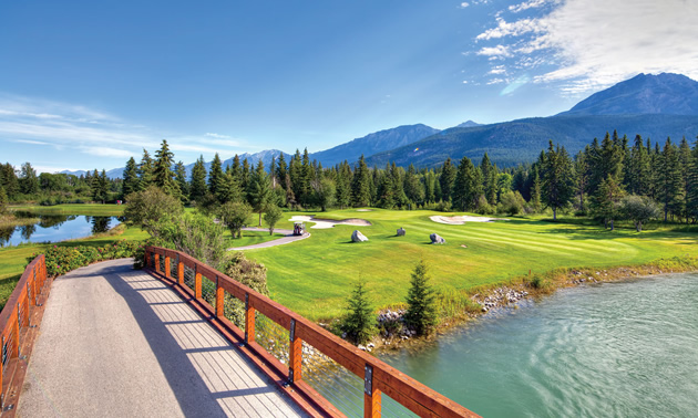Wooden bridge over waterway, with golf course in the background.