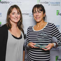 Two women, one holding award