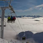 Photo of people sitting on a ski lift.