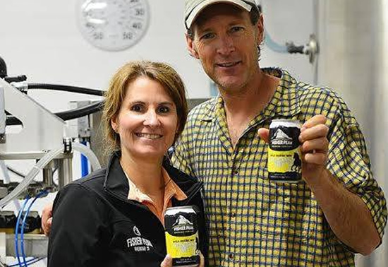 Owners of Fisher Peak Brewing Company holding cans of beer.