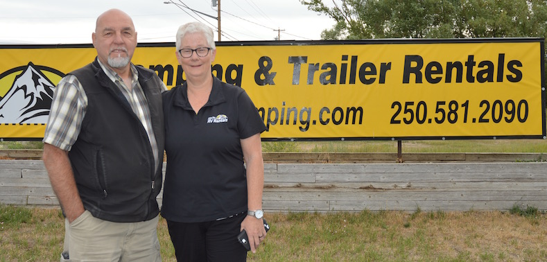 Christie and Menno Dueck standing in front of their Fisher Peak Camping & Trailer Rentals sign.