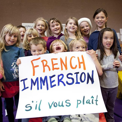 Picture of group of young students holding a sign that says, 'French Immersion - s'il vous plait'