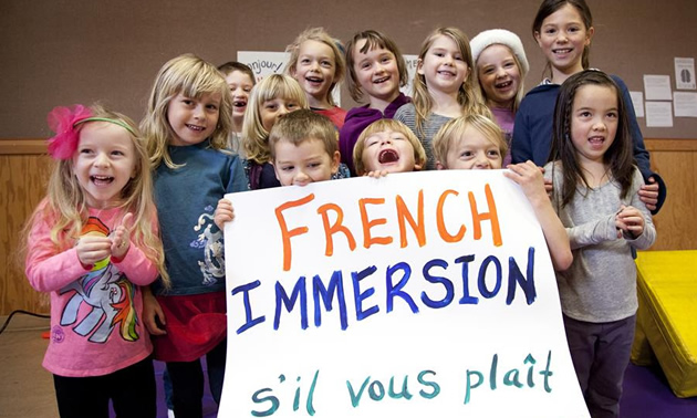 Kids holding up a French Immersion sign.