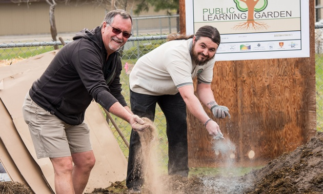 Michael Dean (L) and his son Andrés spread two types of rock dust on the Learning Garden in Grand Forks. Andrés is now general manager of Gaia Green Products.