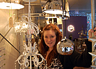 lady standing next to lighting and furniture pieces