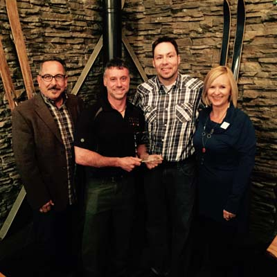 Tom Tischik (left), new chair of Kootenay Rockies Tourism and Kathy Cooper (right), Chief Executive Officer of Kootenay Rockies Tourism present owner Darrin DeRosa and Chef Corey Fraser of the Cedar House Chalets in Golden with the Tourism Business of the Year award.