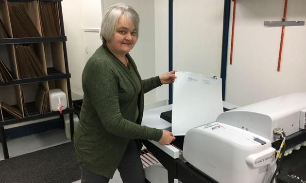 Ingrid Hope, president/owner of Hall Printing, stands beside an environmentally friendly, energy-efficient printer that uses no processing chemicals or water.
