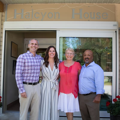 Group shot of four people, in front of doors at Halycon House in Nakusp.