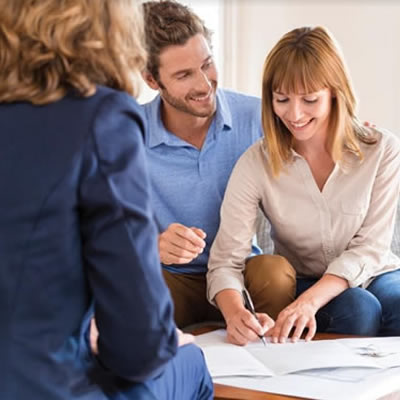 Smiling couple signing papers while realtor looks on.