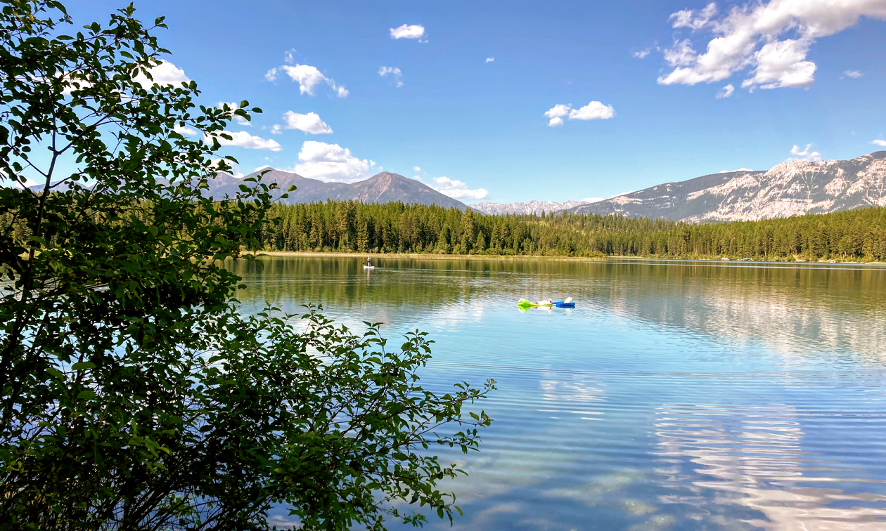 A canoer and people on floats enjoy a calm lake with mountains in the distance and a blue sky.