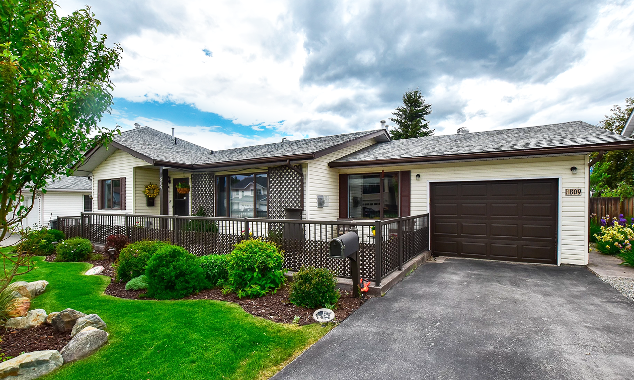 A one-storey tan and brown house with an attached garage has a well-maintained lawn and gardens with shrubs, trees and rocks.