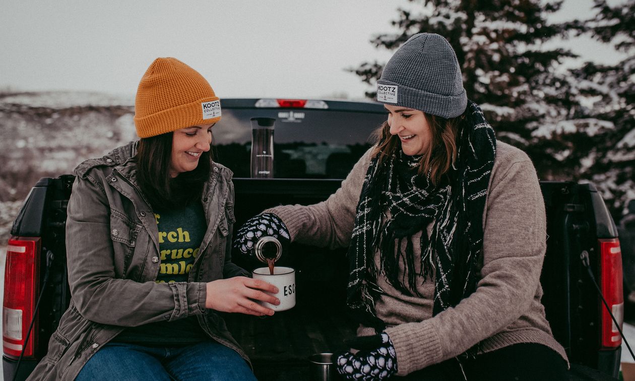 Kelsey Gosse (Left) and Leah Pavlick (right) wearing Kootz Collective merchandise and pouring coffee into a mug