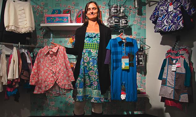 Janet Skolka holding up children's clothing in Nelson, BC