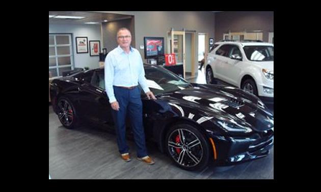 Jim Barber standing beside a black car.
