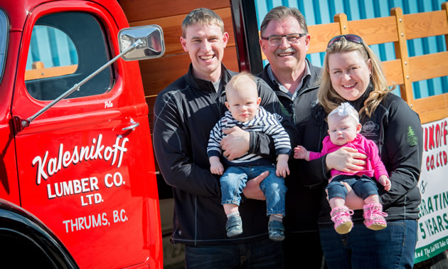 A father, his daughter, son and grandchildren standing by a red truck.