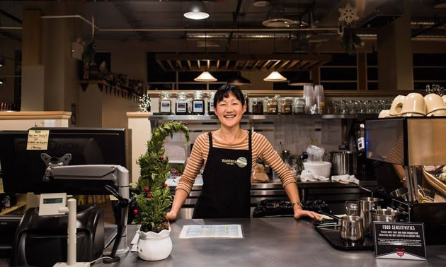 A smiling person at the coffee bar.