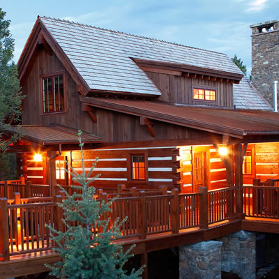 Log cabin-type house, lit up at dusk.