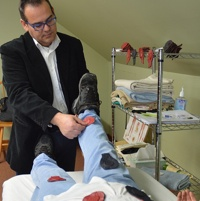 Therapist J. Tomas Gonzalez demonstrating magnetic therapy on a patient.
